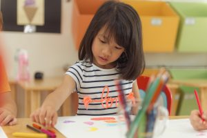 Girl drawing color pencils in kindergarten classroom, preschool